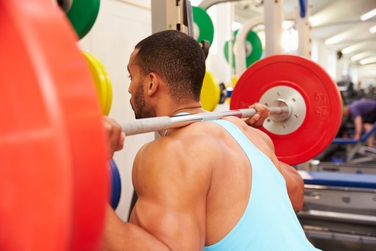 A man preparing to lift a barbell off the squat rack