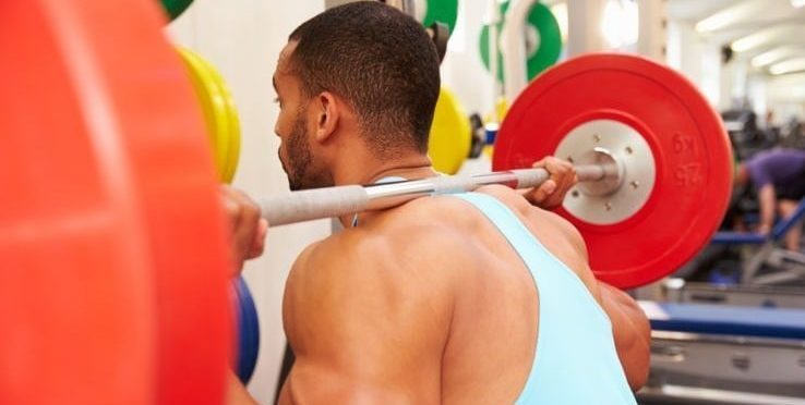 A man starting his squat exercises after lifting the barbell off the squat rack
