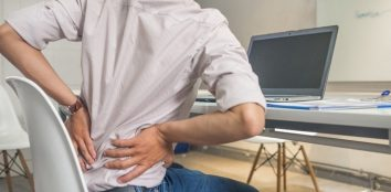 A man sat at his home office having trouble with his lower back