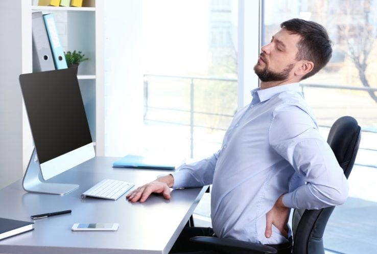 A man sat at his office desk stretching out his bad back