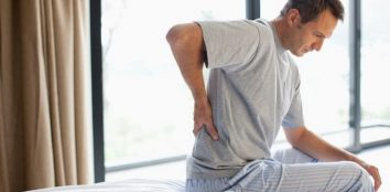 A man sat on his bed having issues with back pain