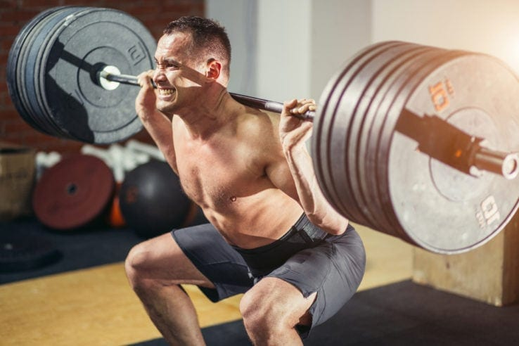 A man struggling to squat with a heavy barbell weight