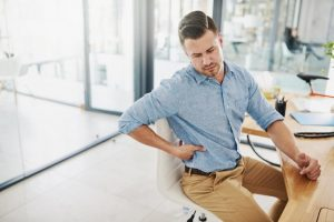 A man suffering from hip pain while sat at his desk