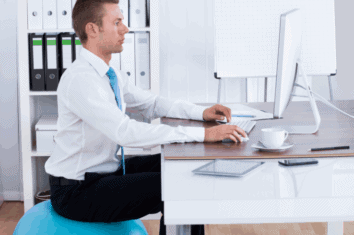 A man using a yoga ball to improve his posture while sat at his office desk