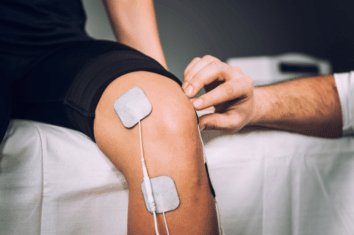 A man using muscle stimulators to treat his knee pain