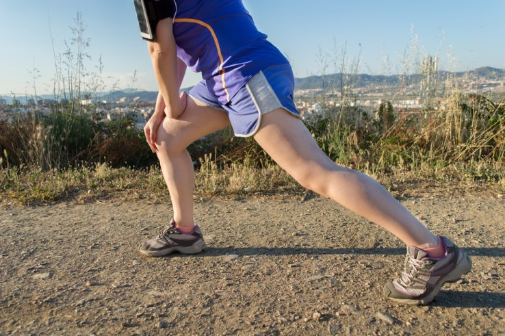 A runner stretching out the legs before a run in the park