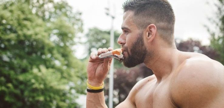 A shirtless man eating a protein bar