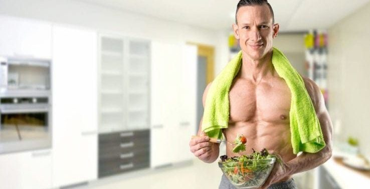 A shirtless man eating salad before he goes to exercise