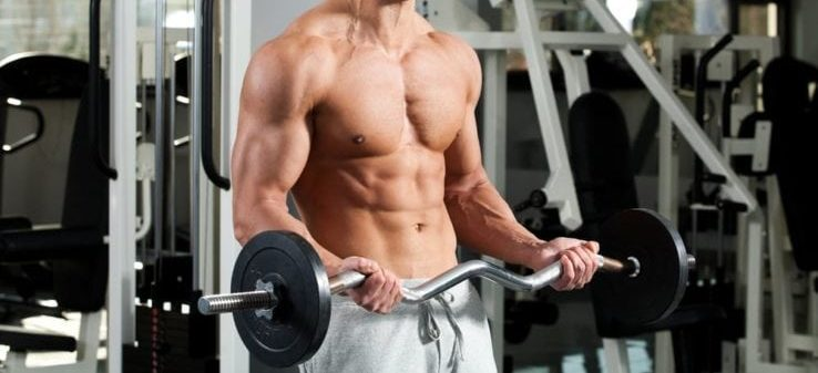 A shirtless man in the gym using a EZ curl bar