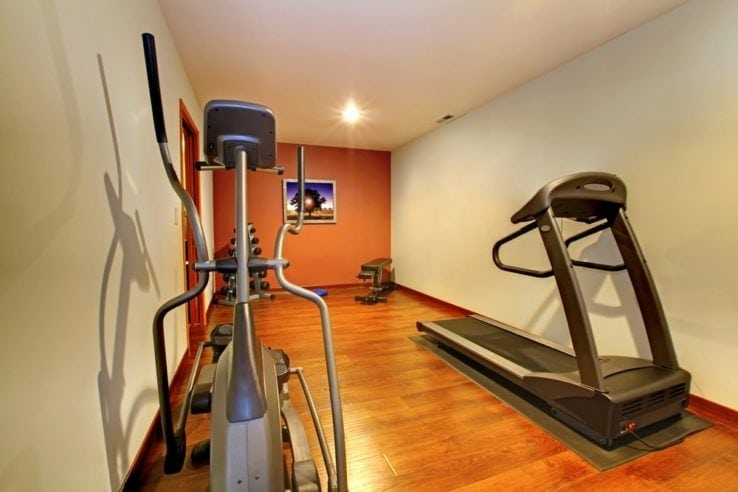 A small home gym with different pieces of gym equipment set up