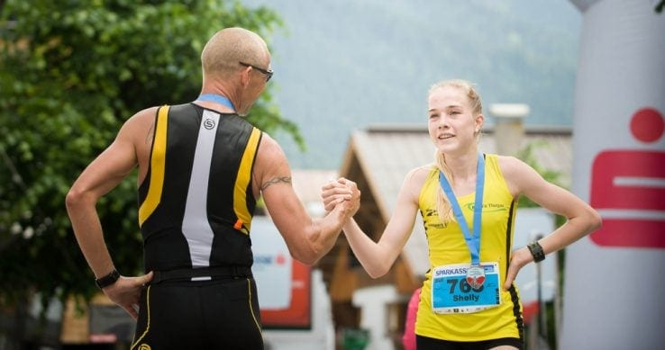 A woman and a man wearing medals after finishing a marathon