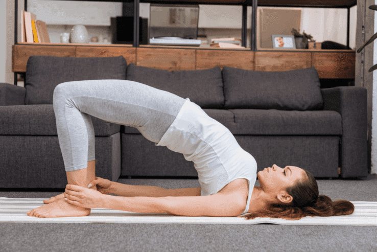 A woman doing a bridge yoga pose in her living room