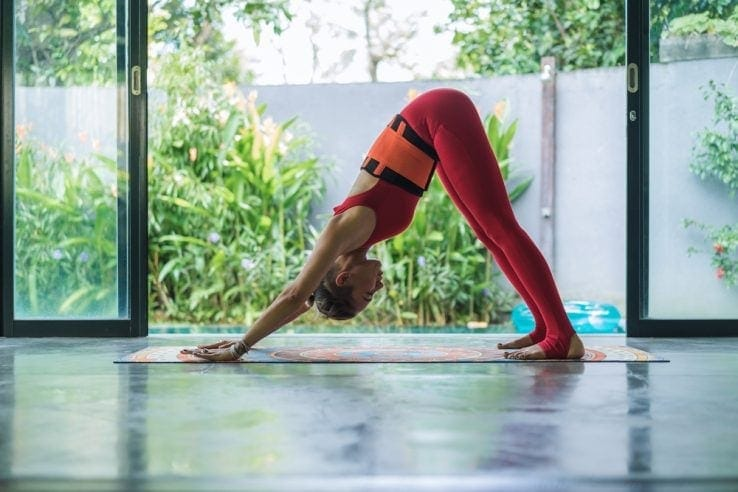 A woman doing a downward dog pose in her home