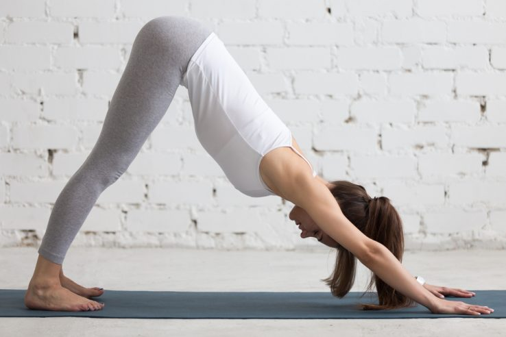 A woman doing a downward dog pose on a yoga mat