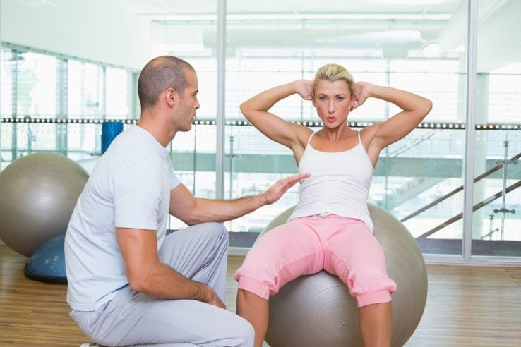 A woman doing core exercises in the gym with her trainer