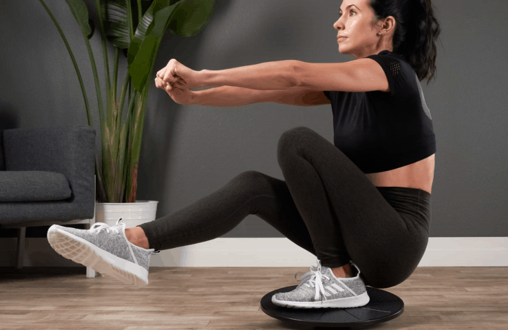 A woman doing core exercises using a balance board