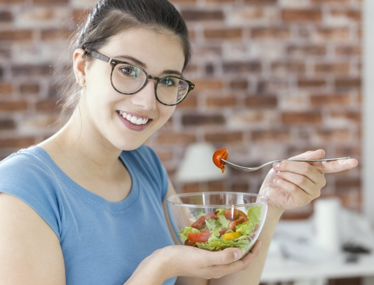 A woman eating a healthy bowl of salad and vegetables