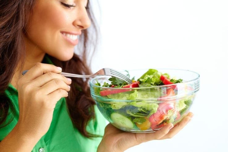 A woman eating a healthy bowl of salad