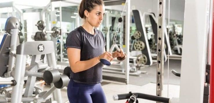 A woman exercising on a machine in the gym
