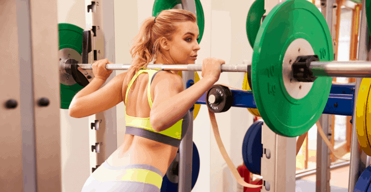 A woman getting ready to lift the barbell weight off a squat rack