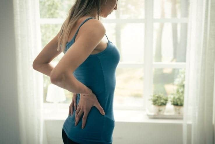A woman holding her lower back as she struggles with the pain