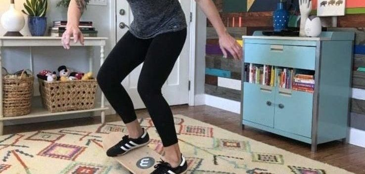 A woman in her home using a balance board