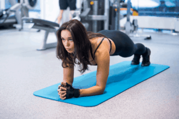 A woman in the gym doing a plank to improve her core