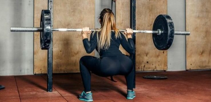 A woman in the gym doing a squat with a long barbell