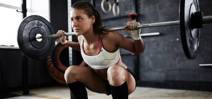 A woman in the gym doing squat exercises with a squat barbell