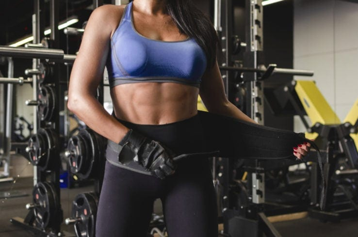 A woman in the gym putting on her weight lifting belt