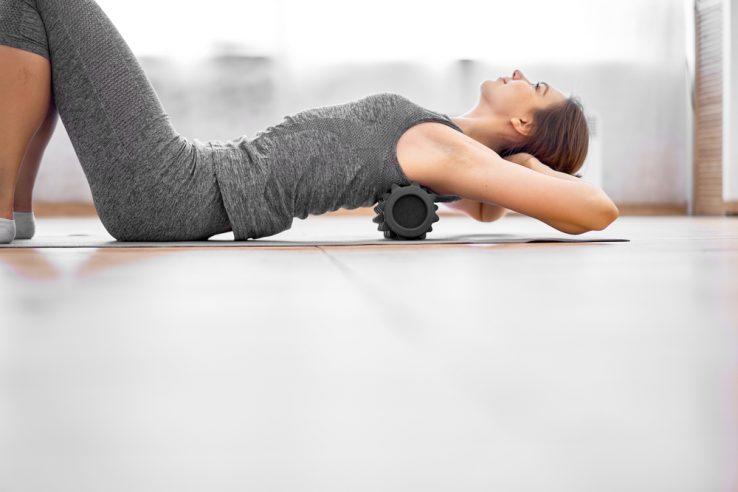 A woman massaging her own back with a foam roller