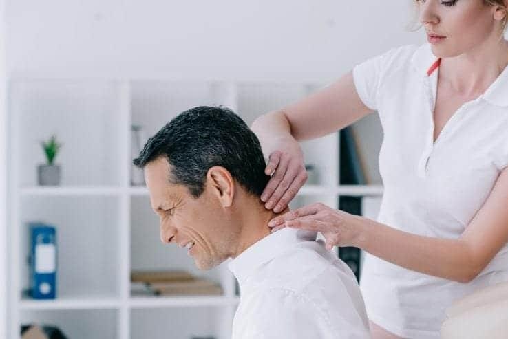 A woman massaging the neck of a man