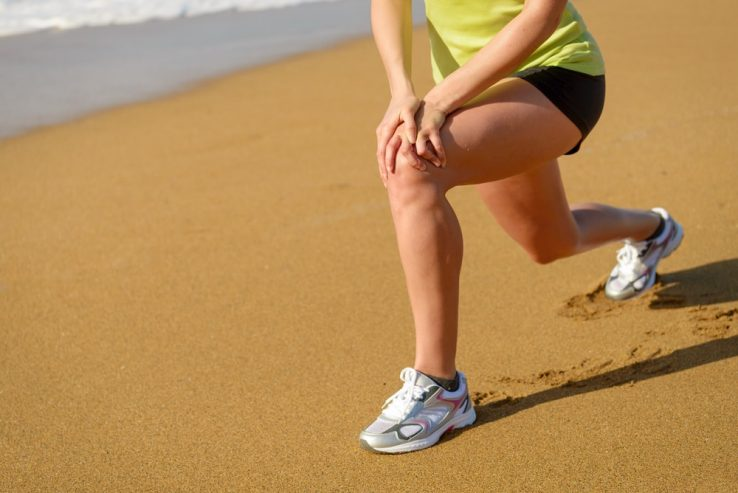 A runner on the beach stretching out her knee