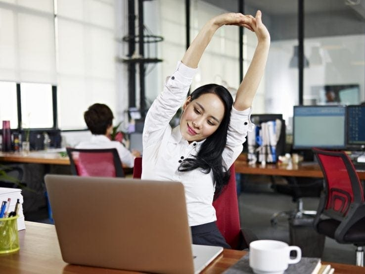 A woman sat at her desk stretching up to the air