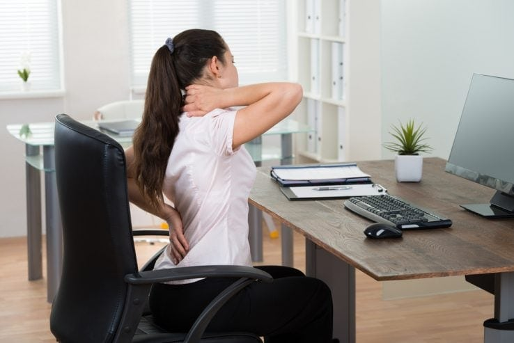 A woman sat at her desk trying to fix her bad posture