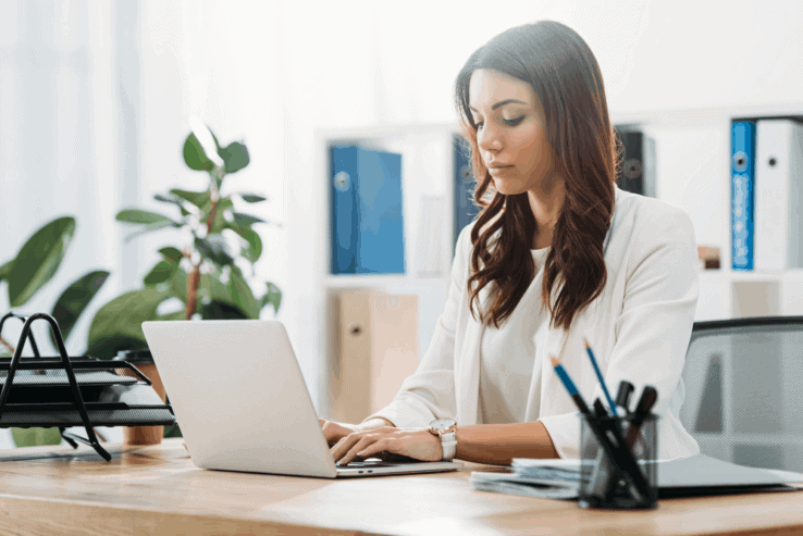 A woman sat at her office desk with good posture