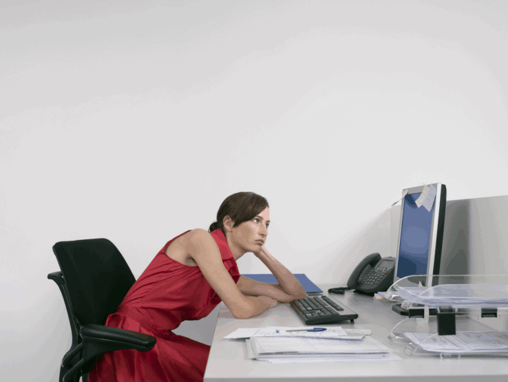 A woman slouching forward in her office chair