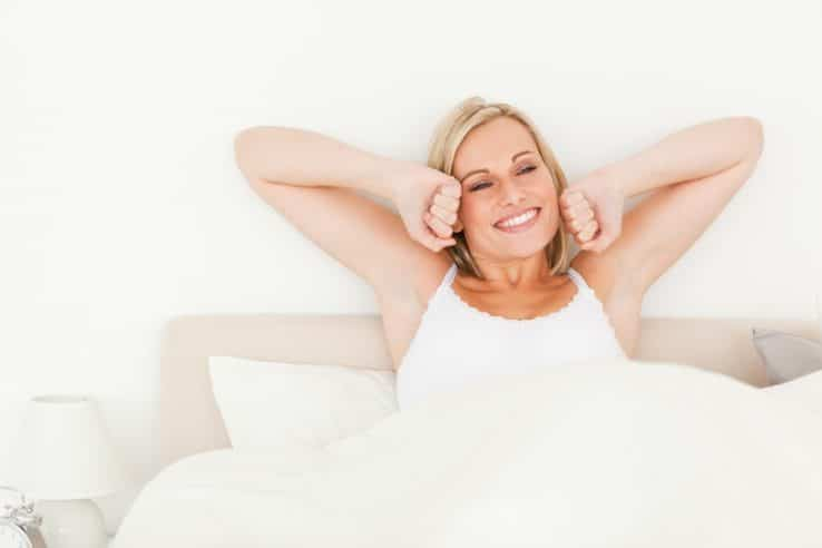 A woman stretching as she wakes up with a smile on her face