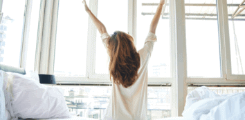 A woman stretching her back as she gets out of bed