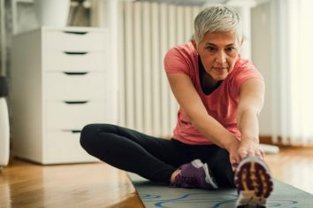 A woman stretching out on her yoga mat at home