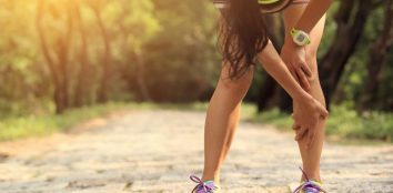 A woman suffering with shin splints while she is running