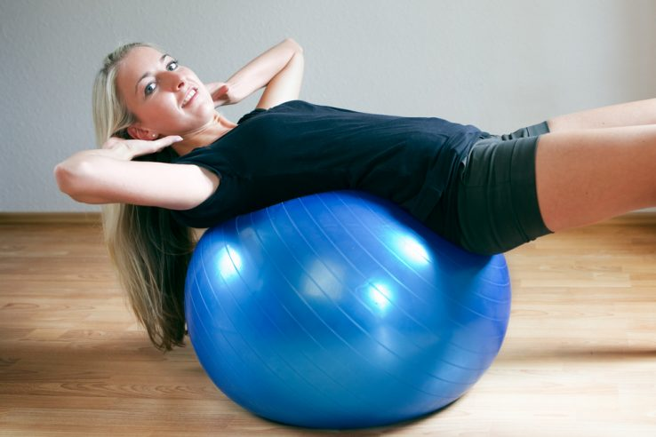 A woman training her core using a yoga ball