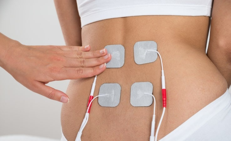 A woman using a electrical muscle stimulation on her lower back