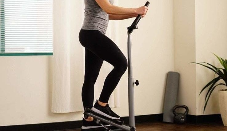 A woman using her stair stepper machine in her home