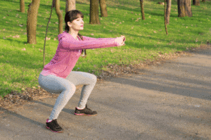 A woman warming up for her run by doing squats