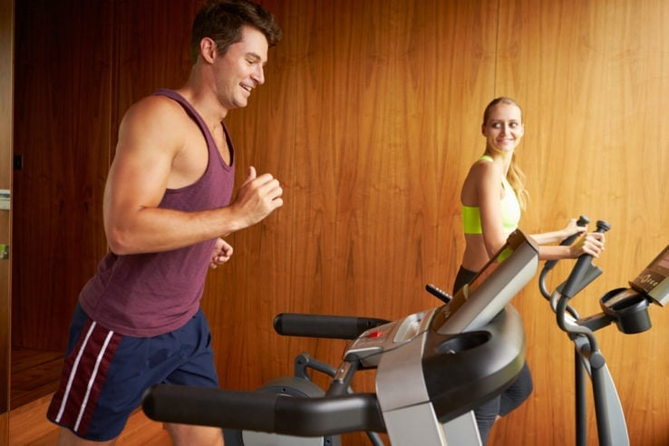 A young couple exercising together in their home gym
