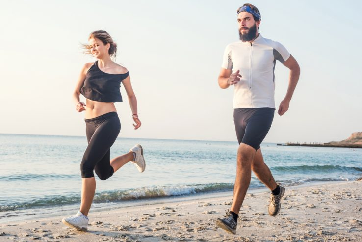 A young couple running together on the beach