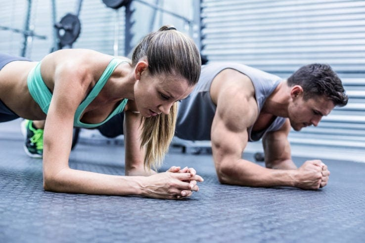 A young man and woman planking together in the gym