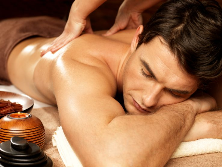 A young man receiving a back massage in a spa