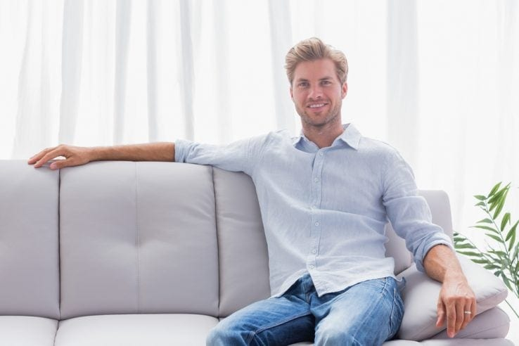 A young man sat up straight on his sofa